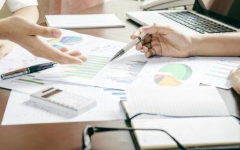 Empresários analisando relatórios em uma mesa.